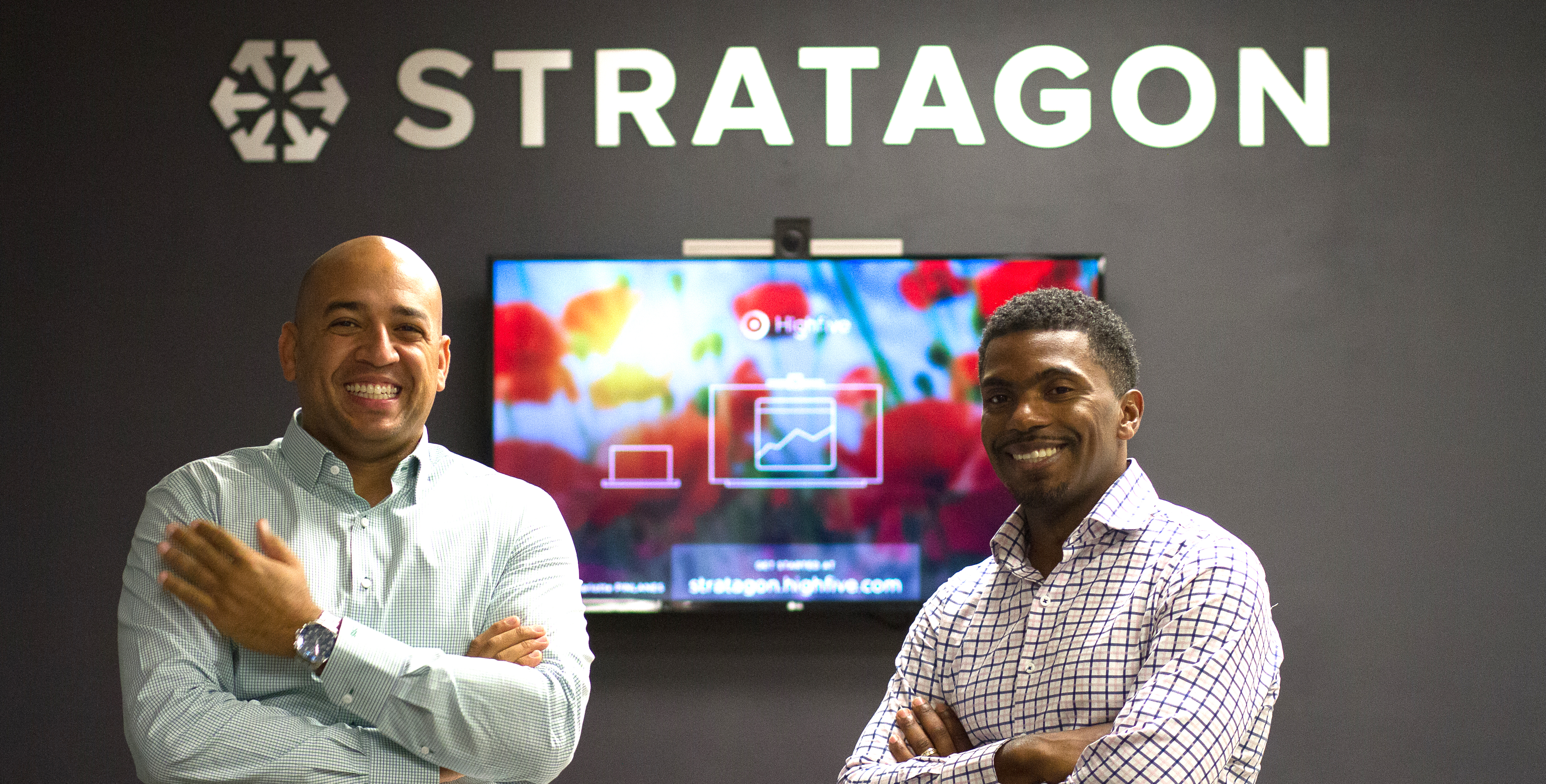 Interviewees Ryan Burkett and Alex Moore stand smiling in front of a wall in their office emblazoned with the company name: Stratagon